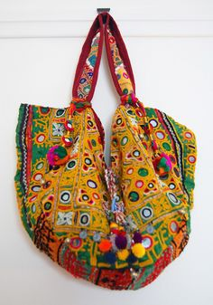 Willow Vintage Indian Embellished Tote Bag (medium)  A hit with stylistas the world over, tribal bags have shot to cult status overnight. This large one-of-a-kind boho carryall has been expertly pieced together from a selection of rainbow bright vintage fabrics from India. Each bag is lavishly embroidered and beautifully decorated with beading, mirrors, tassels, shells, coins, chains and playful pompoms. It features two handles that can be worn on your shoulder or carried by hand.