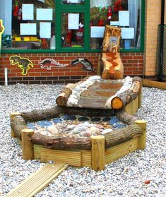 Water play stream created from logs and pebbles in a playground