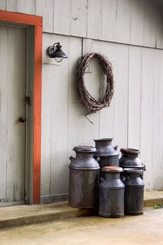 A group of old fashioned milk cans by a farm outbuilding waiting to be picked up, but here, only used for decoration. Most modern people don't know that the smaller cans were used for cream.