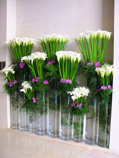 Tiered arrangement using only three kinds of flowers/plants. Would be perfect for an entryway, and would make for a dramatic one.