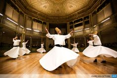 TURKEY, Istanbul : Whirling dervishes perform at the Galata Mevlevihane (The Lodge of the Dervishes) in Istanbul on December 18, 2013. The dervishes are adepts of Sufism, a mystical form of Islam that preaches tolerance and a search for understanding. Those who whirl, like planets around the sun, turn dance into a form of prayer. AFP PHOTO/GURCAN OZTURK