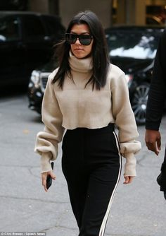 Work it: The reality television star bundled up in a cropped sweatshirt with peeks of her toned tummy popping through as she walked alongside her son