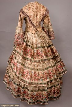 PRINTED WOOL BAREGE DRESS, 1850s Sheer white wool and silk challis (barege) printed in plum and green plaid pattern with red chine roses and green and brown leaves, separate fitted bodice with applied rows of maroon, white and blue fringe, piped, collarless neckline, brass hook & eye back closure, shallow V at center front waist, fitted sleeves with two deep flounces, skirt with shaped waistband and triple en disposition flounces, brown cotton bodice lining, buckram hem facing, (extensive…