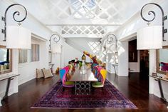 Colorful chairs in white dining room.