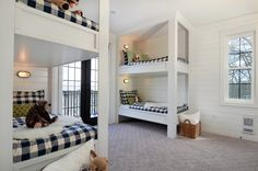 Boy's bunk room with two sets of bunk beds dressed in black and white plaid duvet and shams accented with green quatrefoil pillows over gray quatrefoil rug. Shared boy's room features tongue and groove walls and marine sconces lighting each bunk bed.