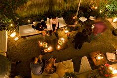 Romantic outdoor lounge with seating area with candles, flowers at night