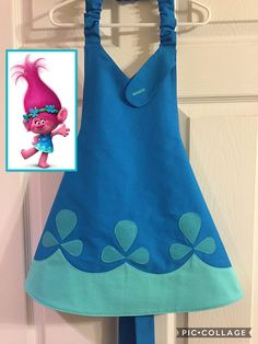 POPPY TROLL INSPIRED APRON This adorable Disney inspired Poppy Troll apron will definitely draw out a little girls imagination. Whether shes pretending to be a cute little troll or trying to be mothers little helper, shes sure to have hours of fun dressing up. Easy on/off with elastic neck strap and back ribbon ties. All fabrics are prewashed before the item is made to reduce shrinking. Care: Machine washable and line dry SIZING: There are three size options. Small size measures approx...
