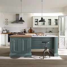 Blue/grey cabinets, bleach washed wooden floors, butcher block counters mixed with white countertops