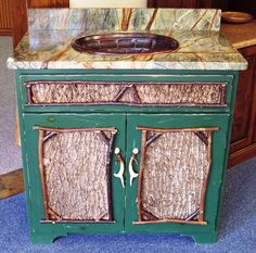 Adirondack style bath vanity with antler pulls, rainforest green marble, and copper sink.