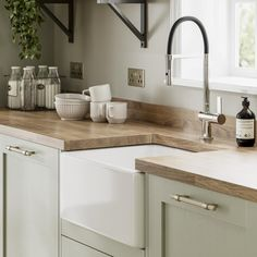 Pale enough to work as a neutral, the sage green tone of these sturdy, 20mm-thick doors makes a great choice for those that want a subtle style with plenty of country character. Choose from a wide variety of cupboards, such as larder units, which can keep cooling devices hidden from view to help maintain an uninterrupted design. Green Country Kitchen, Small Country Kitchens, Sage Green Kitchen, Green Kitchen Cabinets, Country Kitchen Designs, Wood Counter Tops Kitchen, Wooden Worktop Kitchen, Green Kitchen Walls, Kitchen Worktops