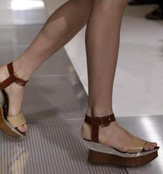 """'At Marni, the flat sandals with layered lucite and wood double-platforms, shown here, reminded one T editor of the work of the Italian architect and designer Carlo Mollino. """"Great mix of materials, plus very architectural, like a piece of furniture,"""" she wrote in. Other footwear options were wedged and heeled (the buff colored pumps with their pointy toes and concise ankle straps made feet look especially elegant), but these shoes cast the strongest spell.'"""
