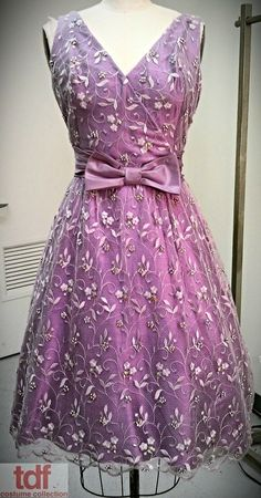 The shade of violet on this cute dress is so eye catching! It's got a cute silhouette and the lace on top with the subtle beading is adorable! It doesn't weigh it down and will make anyone who wears it look younger. #TDFCC #KeepingUpWithTheCostumes #1950s