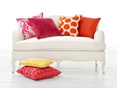 Punch up a white sofa with bright fuschias and oranges. Using these bold colors in accent pillows is a great way to experiment with intense hues without having to make a permanent change.
