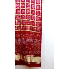 Red gajji silk gharchola bandhani saree. The pallu of the saree has a lagdi patta as shown in the pictures. Blouse piece is included.