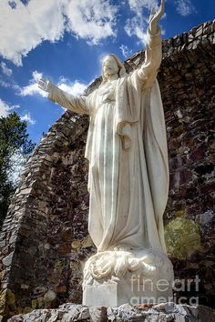 A capture of 'Christ On The Mountain' in Silverton, Colorado.  Illuminated with stars and sunlight.  A 12-ton, 16-foot tall statue of Jesus Christ, sits some 500 feet up the slope of Anvil Mountain, north of town.