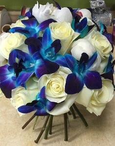 Sapphire - eye-catching bluish purple dendrobium orchids, white standard roses, and white peonies in a hand tied bridal bouquet