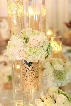Tall clear vases with gold doilies. Would be beautiful with a submersible LED votive!