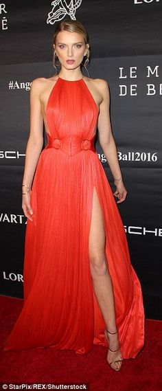 Leggy:The Brit beauty showed off her model credentials in a draped scarlet gown which flashed her endless legs
