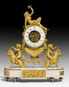"""AMINPENDULE """"A LA BACCHANTE"""", Directoire, Paris um 1800. Matt- und glanzvergoldete Bronze sowie """"Carrara""""-Marmor. Auf Gehäuse liegende Bacchantin, getragen von 2 Widder reitenden Amoren auf perlstabbeschmücktem Bastionssockel mit Kreiselfüssen. Emailzifferring mit arabischen Stunden- und Minutenzahlen sowie Datum. Ankerwerk mit ½-Stundenschlag auf Glocke. 3 feine, teils durchbrochene und vergoldete Zeiger. Feiner Pendel mit Trauben und Ranken. Zifferblatt leicht bestossen."""