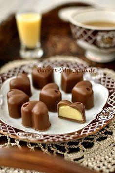 Zutaten: 180g weiße Schokolade 50ml Eierlikör 240g Vollmilchschokolade Zubereitung: Vollmilchschokolade klein hacken und im Wasserbad schmelzen lassen. Die Mulden der...