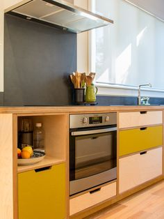 Contemporary kitchen in a classic Villa, with strong use of colour that is offset by the softness of the plywood and black Laminam worktop.