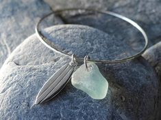 Saltwater Souls by Sea Gypsy A handmade hammered sterling silver 925 bangle decorated with a beautifully unique piece of seafoam/aqua coloured sea glass collected from the North Devon coast and a sterling silver surfboard.