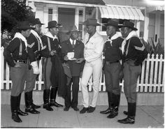 "The modern 10th Cavalry visited Lt. William M. Dunn (center), veteran of the original U.S. Army unit. Dunn joined the 10th Cavalry, known as the ""Buffalo Soldiers"" in 1898. The 94 year old ex-horse soldier was one of 17 men who won field commissions during the Spanish American War.  The 10th Cavalry was re-created by a group of young men with authentic uniforms, riding, and preparing to appear in a motion picture. Institute for Arts and Media Photographs."