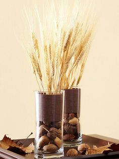 Filled Up - Layering and incorporating various elements are key to an eye-catching fall display. To create this look, fill vases partway with nuts. Cut a piece of scrapbook paper to fit inside the vase and arrange shocks of wheat or other branches in the vase.