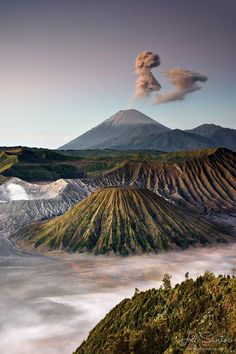 Volcanic vents inside the Tengger caldera on the island of Java, Indonesia. In the foreground is the inactive Batok cone with Mount Bromo (7,641 ft or 2,329 m) smoldering to its left.