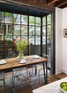 Hanson General Contracting created this breakfast nook in West Philadelphia by installing a floor-to-ceiling bay window at the end of a bright white kitchen. The three walls of glass visually extend the interior space of the historic home into the back ga