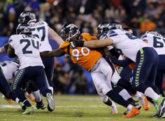 Denver Broncos defensive end Shaun Phillips (90) reaches to tackle against Seattle Seahawks running back Marshawn Lynch (24) during Super Bowl XLVIII at Metlife Stadium on Sunday, Feb. 2, 2014, in East Rutherford, N.J. (Ric Tapia/NFL)