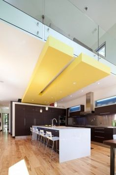 A bold yellow ceiling juts out from below the usual white drywall in this kitchen. A slot in the yellow surface receives the pendant lights hanging over the island.