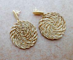 Brinco em capim dourado; mandala trançada; base de metal dourado.