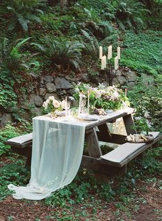 the linen on the tables + greenery + tall candles really makes the picnic table vibe extra beautiful