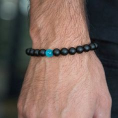 From Benevolence Los Angeles, this water drop bracelet is a unique piece. The comfortable elastic design comes together in matte black onyx beads, with a stylish blue cat's eye bead taking center stage. Cat's eye stones and beads bring luck and protect the wearer from all forms of negativity. <br>  <ul>  <li>Available in medium and large sizes</li>  <li>Unique handcrafted design</li>  <li>Comes in an eco-friendly cottage pouch, ready...