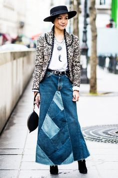 A printed jacket is paired with a white tee, layered necklaces, a long denim skirt, black wristlet, and suede booties