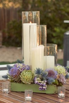 Staggered candles and assorted succulents make a perfect centerpiece