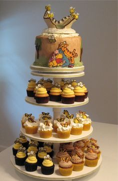 "Winnie the Pooh - Cake, cupcakes and assortment of miniature treats for my neice's baby shower.  Baby's bedding is called ""Days of Hunny"" , used as inspiration for colors/characters. Also want to thank Hansel_Gretel for the inspiration of the adorable baby cake posted.  I shamelessly stole that idea for this topper.  All buttercream, chocolate transfer Pooh characters, fondant trees on cake, gumpaste & fondant topper.  Cupcakes had chocolate transfers on top.  Thanks for looking."