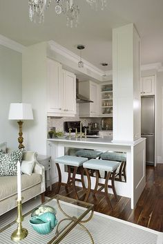 Small kitchen with cutout. Mirror behind stools