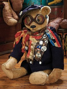 """Grand-Sized Vintage """"Political Teddy"""" Germany,1920s,the bear wears a wonderful vintage costume of black wool jacket that is laden with many vintage political buttons,medallion badge,The Acme Thunderer brass whistle,goggles,studded leather collar,and blue woolen cap with vintage button """"Keep U.S. Out of War""""."""