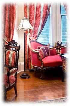 The lush red curtains and Eastlake chair and sofa really set this room off.