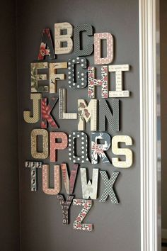 Cardboard letters covered with different patterns. Placed vertically on the wall between the crib and bookshelf.