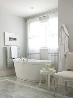Sarah's Suburban House: New Home, Classic Style A Place to Unwind | hgtv.com | Sarah's House star Sarah Richardson used full-length curtains to give the illusion of a picture window behind the soaking tub.  A patterned table holds bathtime essentials.