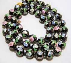 Vintage cloisonne enamel beaded necklace Black back ground with pink and green flower design 12 mm beads, 29 inches long Gold tone clasp, each bead is hand knotted Unsigned Very good vintage condition I specialize in vintage beaded jewelry, please visit my shop to see more I do my best to only sell top quality, well maintained jewelry, please visit my other treasures International buyers welcome, shipping is automatically combined, overcharges are refunded Flat rate priority shipping is…