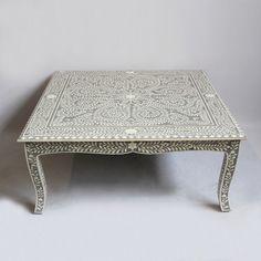 Intricate white bone inlay work with cement gray ground.