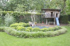 Leeftuin met een trampoline omringd door struiken