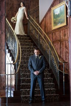 Groom waiting at the bottom of a vintage staircase for the first look at his bride @myweddingdotcom