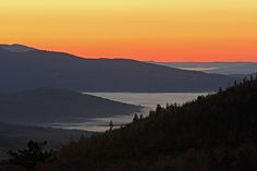 This photo from the New Hampshire White Mountains features a spectacular sunrise view photographed from one of the vista turnouts along the Kancamagus Highway in Northern NH. The sun rises across one of the scenic mountain ridges at the Pemigewasset Wilderness valley while the sky and fall foliage is painted in beautiful pastels.   Good light and happy photo making! Juergen   Fine Art Prints: www.RothGalleries.com  Image Licensing: www.ExploringTheLight.com  www.facebook.com/naturefineart