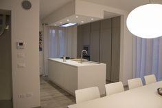 Cucina lineare finitura isola laccato bianco, colonne dispensa tortora. Piano a gas color bianco, lavello acciaio, cappa incassata al soffitto.
