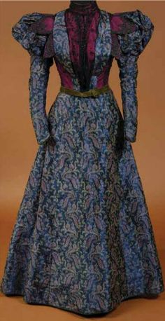 Day dress, Daisy Schaeffer, Columbus, OH, ca. 1897-98. Paisley silk warp print in purple, pink, & green. Bodice has bright magenta taffeta covered with black netting trimmed with black glass beads. Gigot sleeves finished with narrow band of green velvet that is repeated in narrow waist sash. Ohio State Univ.